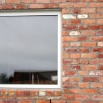 Modern picture window in a recycled brick exterior wall